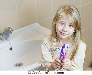 Two different toothbrushes in the girl's hands. The concept of oral care.