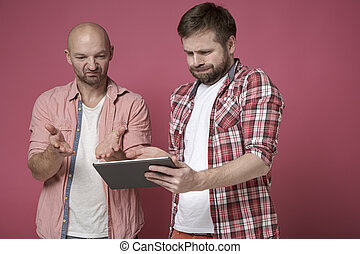 Two displeased men are looking at the tablet, they are disappointed with what they saw and are upset.