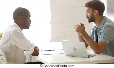Two diverse african and caucasian businessmen talking negotiating in office