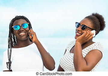 Two diverse african teens talking on smart phones.