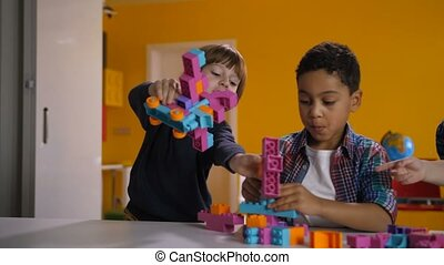 Two diverse kids arguing over toy in kindergarten