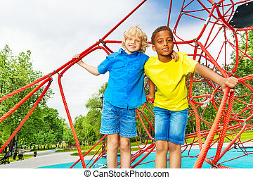 Two diverse looking boys stand close on red web