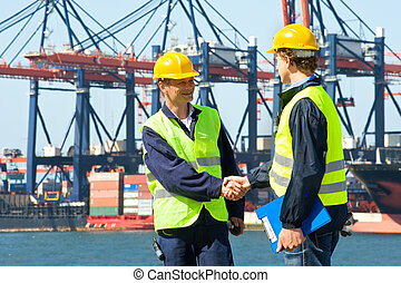 Two Dockers - Two dockers shake hands in front of an...