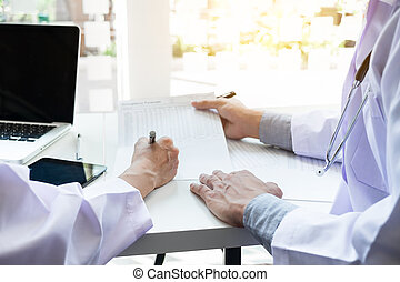 Two doctors being discussing patient history in an office...