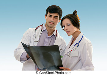 Male and female doctors in work uniforms confer over the results of a patient chest x-ray.