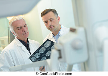 two doctors examining an x-ray