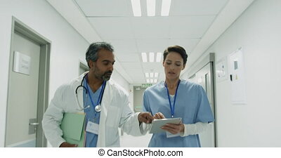 Two doctors in discussion walking in hospital corridor 4k