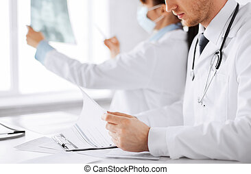 two doctors looking at x-ray - healthcare, medical and...