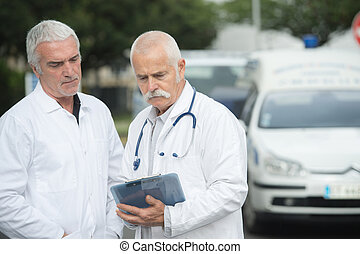 two doctors outside in front of ambulance