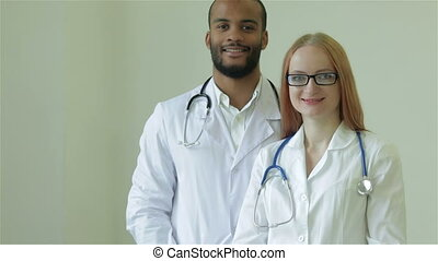 Two doctors put her arms and smiling at the camera