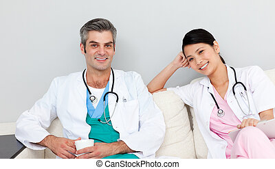 Two doctors relaxing and drinking coffee