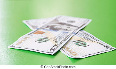 Two dollar bills on a green background