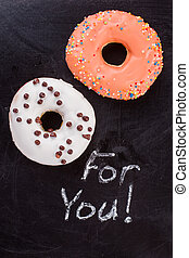 Two donuts on black background.