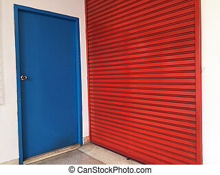 Two doors next to each other, small blue wooden door and big red metal door. blue for people and red for large stuff.