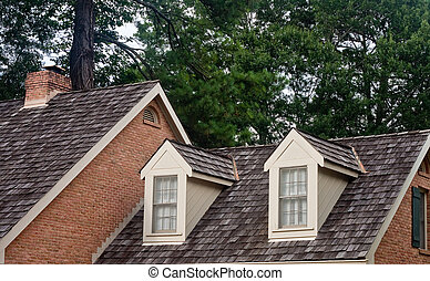 Two dormers on the roof of a wood shingled home