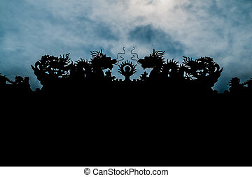 Two dragons facing each other in silhouette