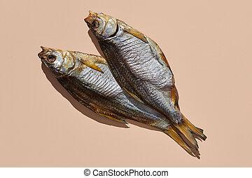 Two dried or jerky salty taranka, yummy clipfish on pink ...