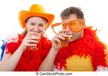 Two Dutch soccer fans in orange outfit cheering for the soccer games with glasses beer, over white background