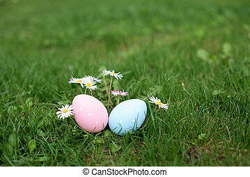 Two easter eggs, ping and blue, in a grass