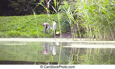 Two ecologist getting soil samples from the bottom of the...