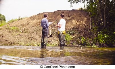 Two ecologists checking with the GPS navigator - Two...