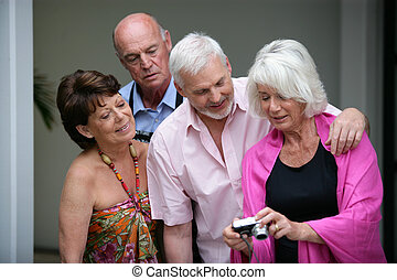 Two elderly couple looking at photos on digital camera