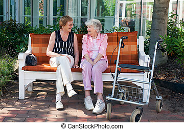 Two elderly friends chatting on a park bench - Two elderly...