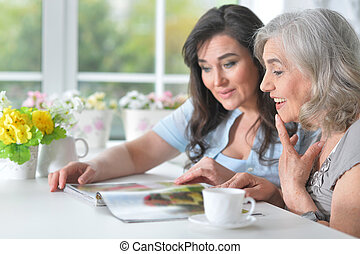 Two elderly girlfriends are reading a magazine