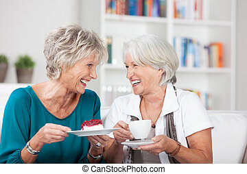 Two attractive elderly ladies enjoy a cup of tea sitting chatting and laughing together in a living room