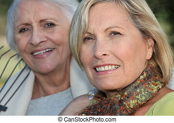 Two elderly ladies sat in the garden together