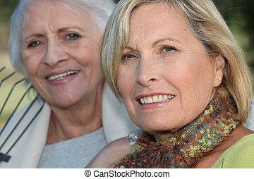 Two elderly ladies sat in the garden together