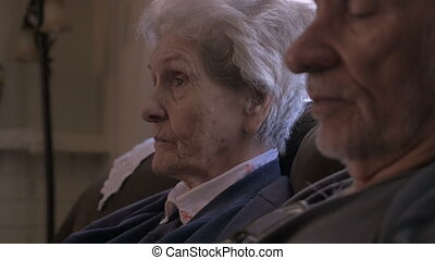 Two elderly older people talking while sitting next to each other on a sofa