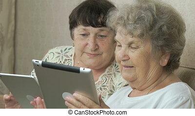 Two elderly women holding the digital tablets - Two elderly...