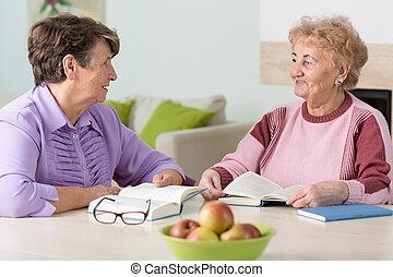 Two elderly women reading