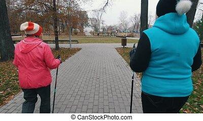 Two elderly women walking on sticks of nordic walking on a sidewalk