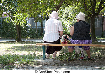 Two elderly womens seated on a bench