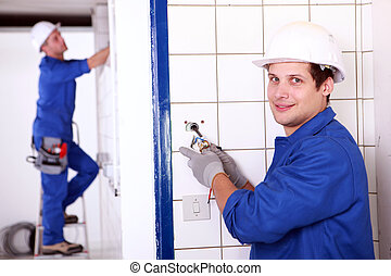 Two electrician fixing electrics in bathroom