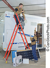 two electricians installing solar panels on rv roof