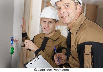 two electricians plumbing socket