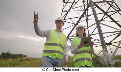 Two electricians work together, standing in the field near...