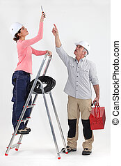 Two electricians working on ceiling lighting