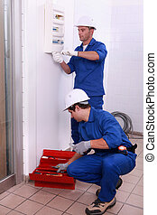two electricians working,  one is setting an electricity meter