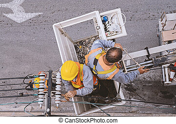 Two electricians working with wires