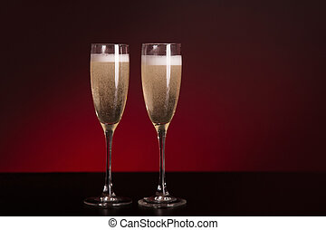 Two elegant champagne glasses on glamorous red background