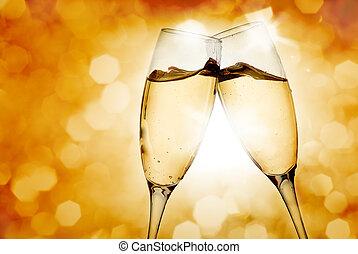 Two elegant champagne glasses on golden background
