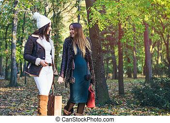 Two elegant young woman walking through a park