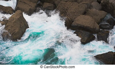 Two elements. the waves of the sea rolled on coastal rocks.