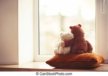 Two embracing teddy bear toys sitting on window-sill - Two ...