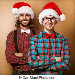Two emotional Santa Claus dressed in clothes hipster standing near a wall - copy Space