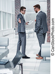 two employees discussing standing in the office